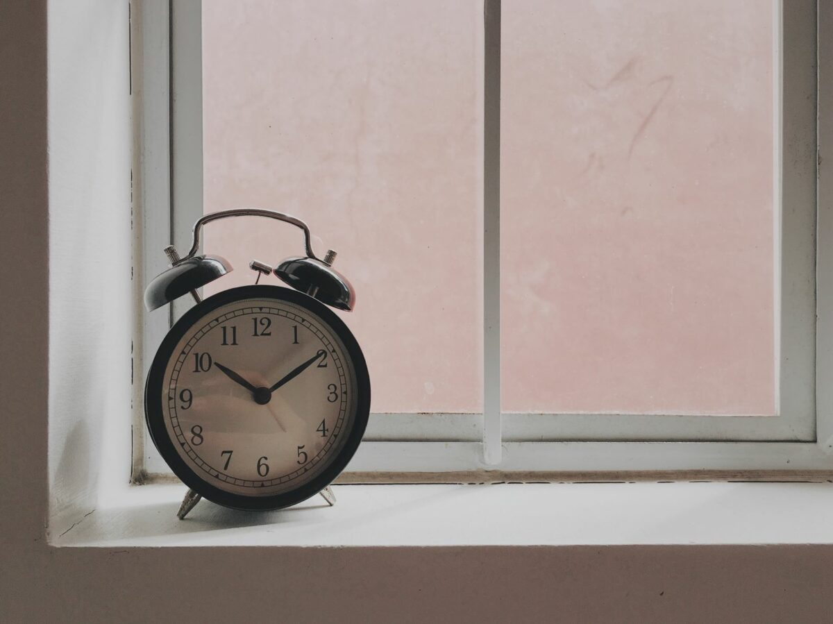 A photo of an alarm clock on a windowsill