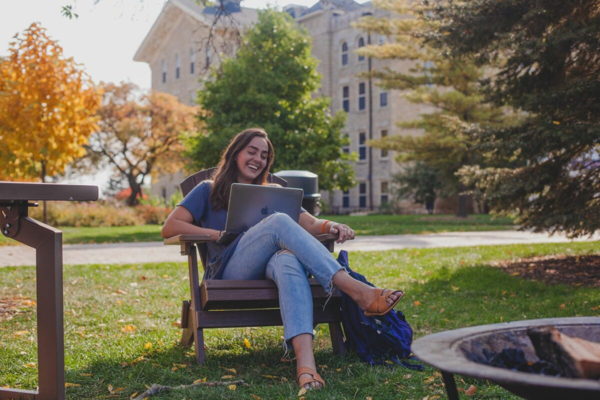 A photo of a Wheaton student outside Blanchard Hall conducting a Writing Consultation from her laptop