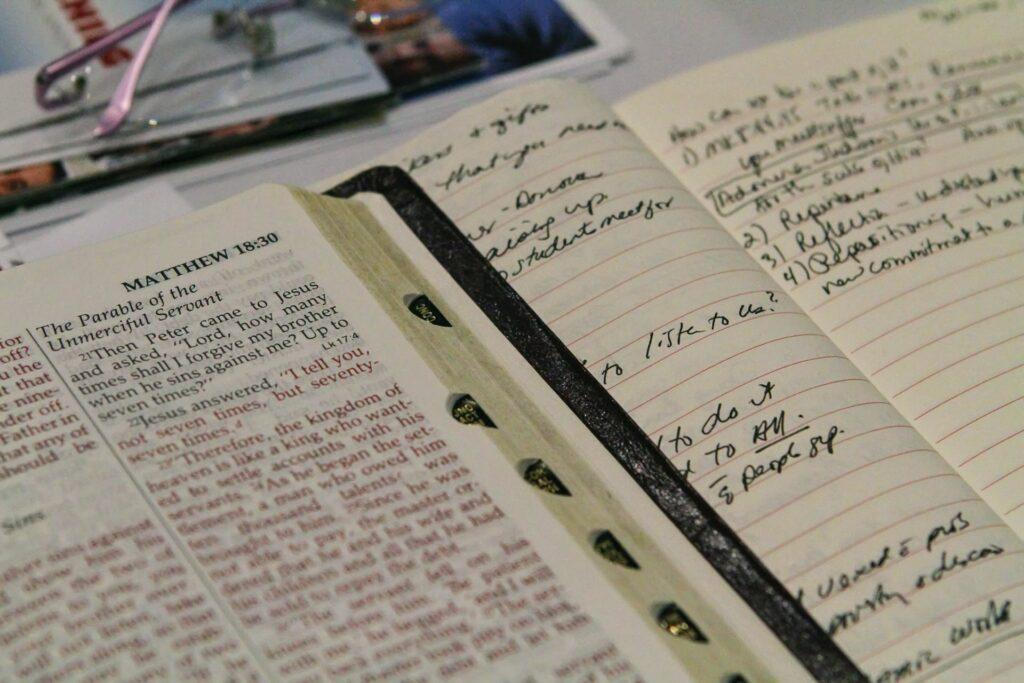 A photo of an open Bible next to a notebook