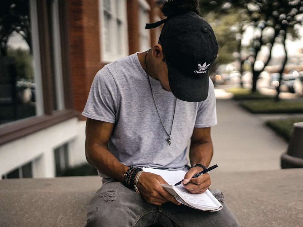 A photo of a man in a black baseball cap sitting down writing in a journal